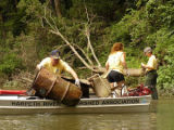 Volunteers load debris into a boat during a river cleanup with the Harpeth River Watershed...